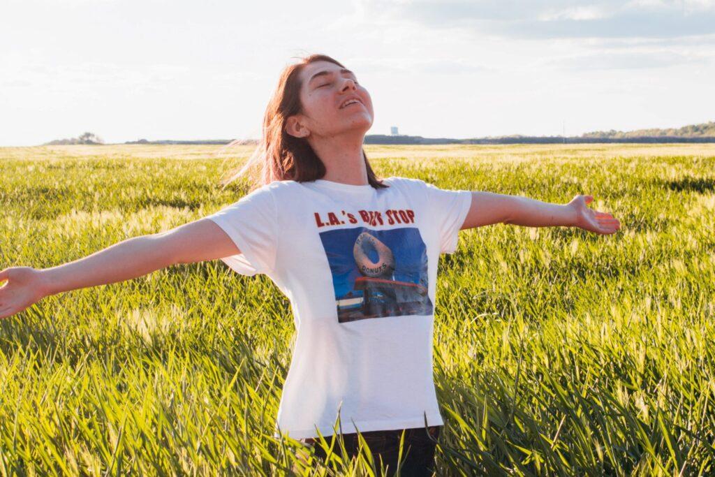 Frau steht mitten in einem Feld, die Arme weit geöffnet und atmet mit geschlossenen Augen