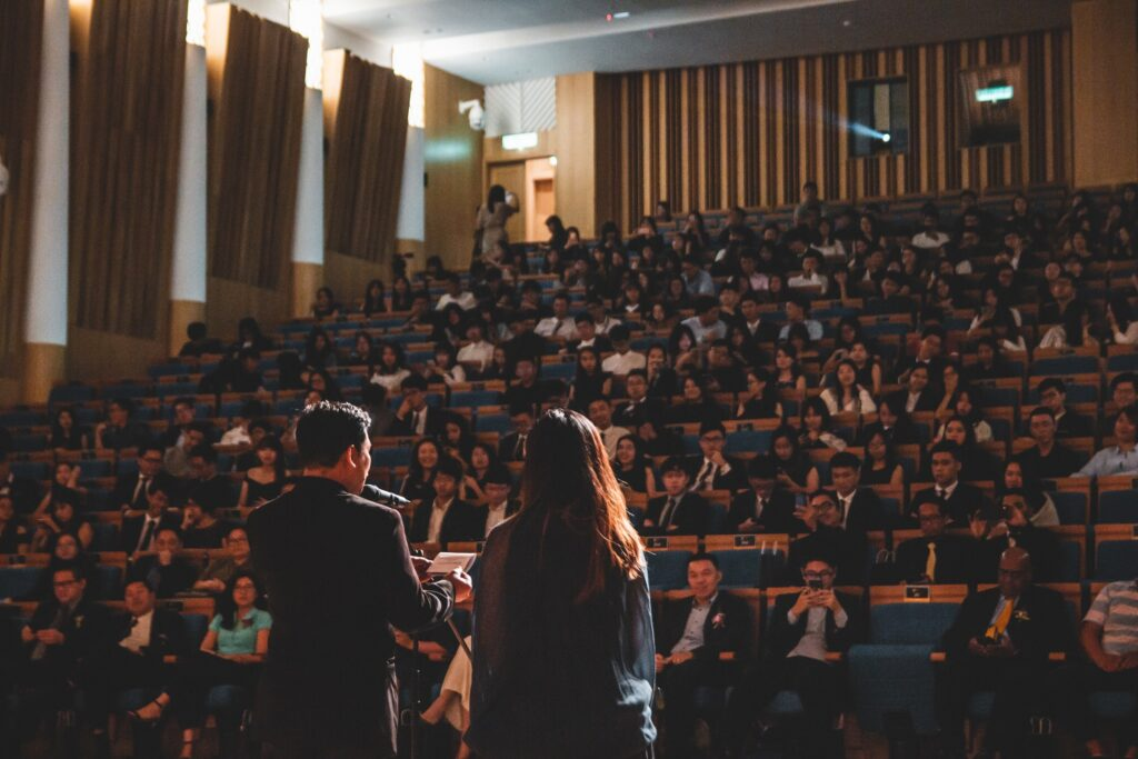 Mann spricht auf Bühne in Mikrofon neben einer Frau und viele Menschen hören zu